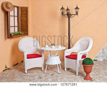 White wicker furniture Rattan European internal courtyard. Street light.