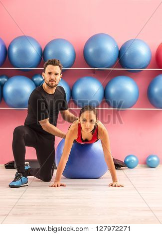 Young woman helped by her coach is training with a ball in a gym.