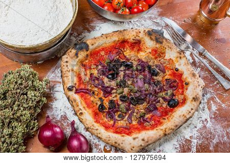 Traditional Italian Pizza With Tuna, Onions, Caper And Olives, On A Wooden Table With The Ingredient