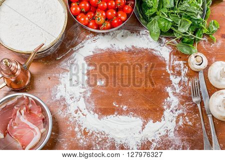 Empty space on a wooden table with pizza ingredients
