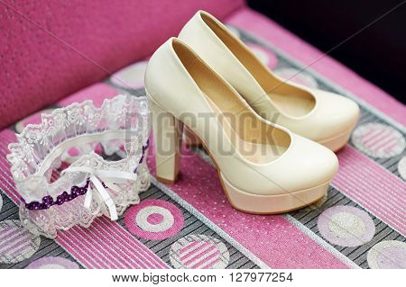 Brides shoes and garter on wooden table.