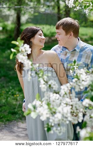 Attractive young couple on a spring garden walk in the countryside in front of a tree covered in white blossom