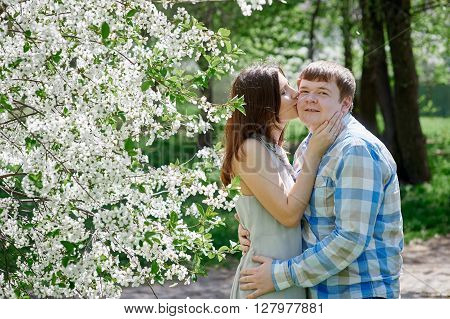 Love and tenderness. woman kissing a man in the blossoming spring garden