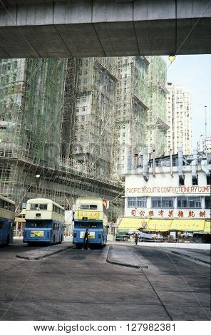 HONG KONG - CIRCA 1987: Double-decker buses are parked at a bus depot in front of the Pacific Biscuit and Confectionery Company