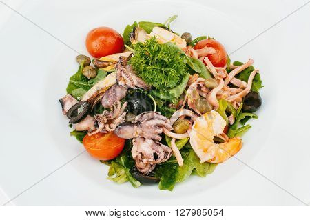 Fresh mixed salad with shrimps octopus olives and pickled capers isolated on white bachground