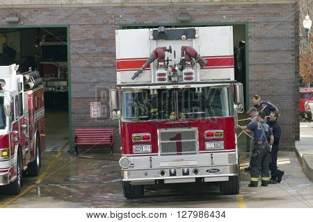 Asheville North Carolina USA - January 8 2016: A group of industrious firefighters team up to scrub down a firetruck at a Fire Station on January 8 2016 in downtown Asheville NC