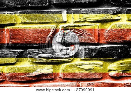 Brick wall Uganda flag with some cracks and vintage look