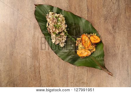 Dried meat risotto with plantain. Wood background.