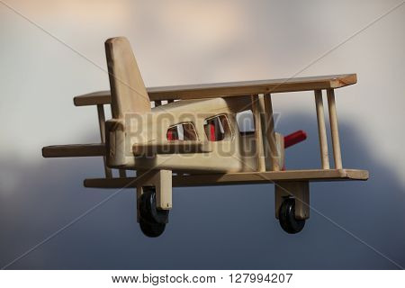 Wooden plane flying under the stormy sky -  Going away
