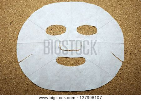 Facial mask on cork message board/bulletin board.