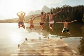 Young Friends Jumping Into Lake From A Jetty poster