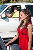 stock photo of peeping-tom  - Young pretty woman in bright red dress unlocks her car door as a man watches stalking in the background from his pickup truck - JPG
