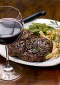 stock photo of red wine  - a juicy rib eye steak dinner with red wine - JPG