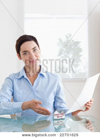 Gorgeous Woman Holding Papers Showing A Model House