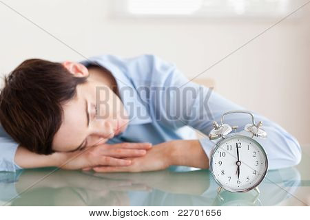 Sleeping Brunette Woman With Her Head On The Desk Next To An Ala