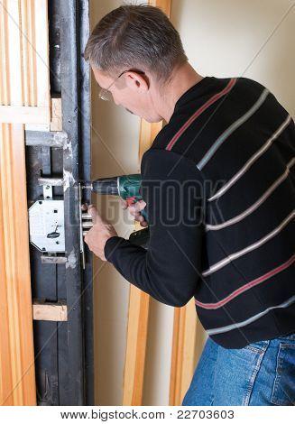 handyman repairing lock with drill