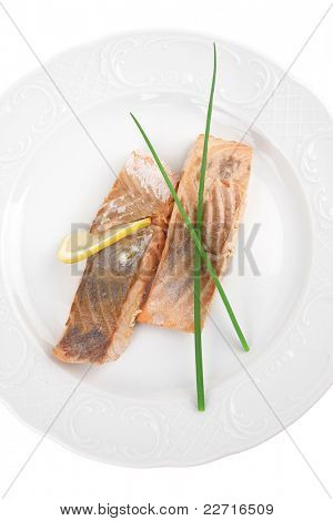 savory sea fish entree : roasted salmon fillet with green onion, and lemon on white plate isolated over white background