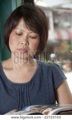 Asian Woman Reading A Magazine
