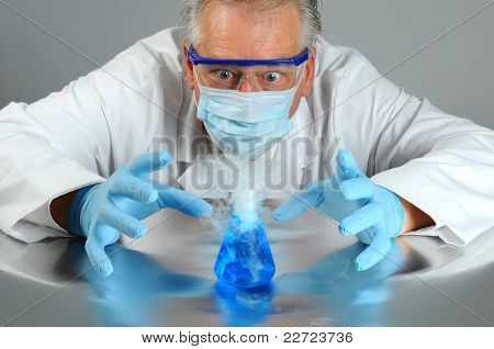 Closeup of a mad scientist as he observes a chemical reaction in his laboratory. Man is partially hidden behind a glass beaker that is bubbling over and smoking.