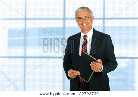 Smiling middle aged businessman in modern office setting holding a small binder. Horizontal Format.