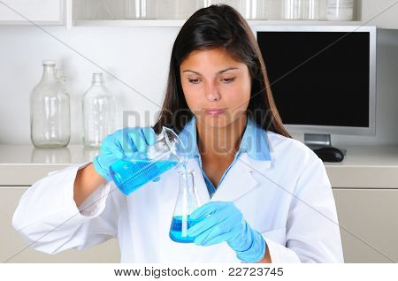 Young female Lab Tech holding up a flask of blue chemicals in laboratory setting. Horizontal format.