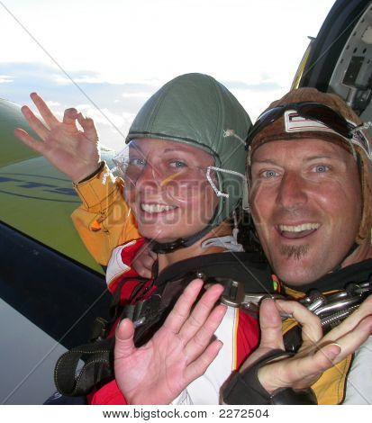 Two Skydivers Waving From An Aeroplane Doorway Before Skydiving
