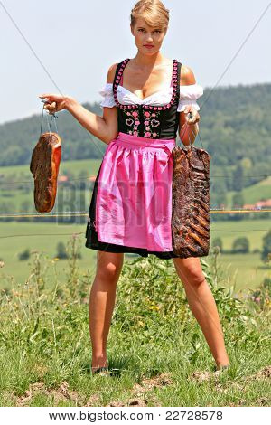Young woman in dirndl with bacon