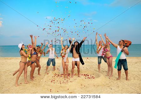 Beach wedding of happy newlywed couple around their friends