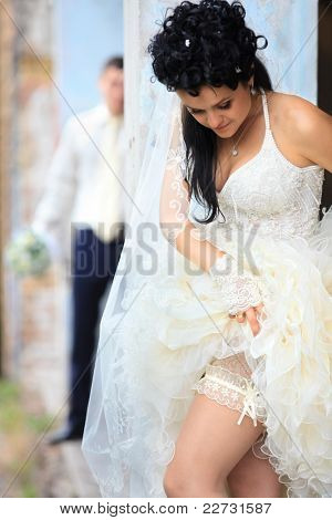 A bride putting on her wedding garter against old grunge place