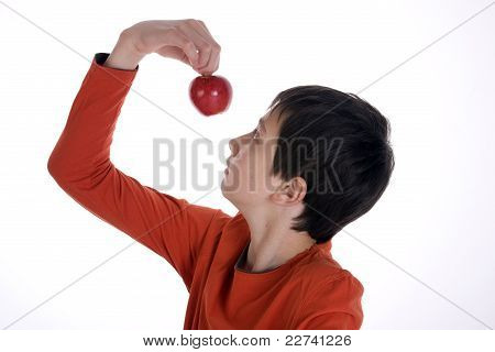 Boy looking at a red apple