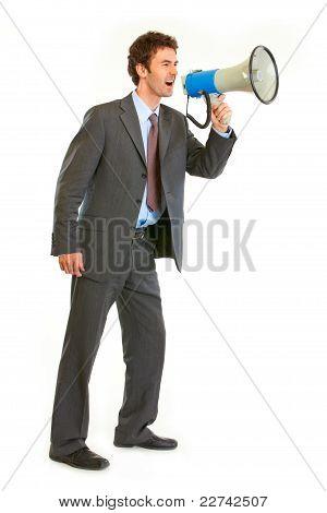Full Length Portrait Of Frustrated Modern Businessman Yelling Through Megaphone