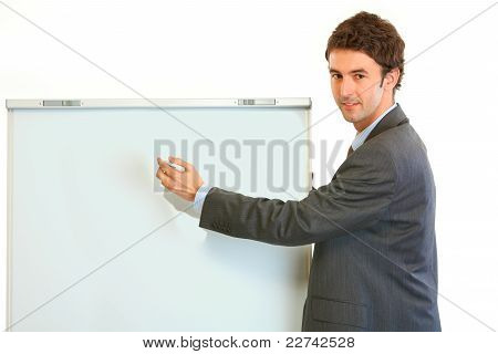 Smiling Modern Businessman Giving Presentation Using Flipchart; Place For Text