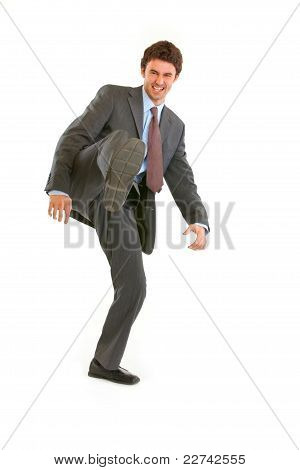 Full Length Portrait Of Very Angry Young Businessman Hard  Kicking