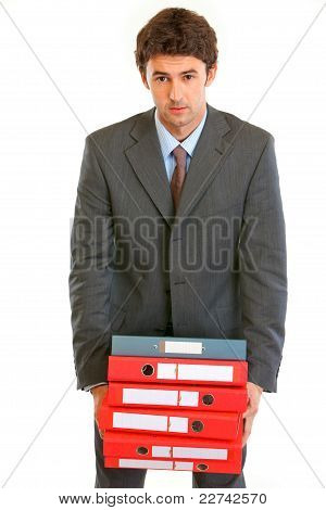 Stressful Young Businessman Holding In Hands Heavy Pile Of Folders