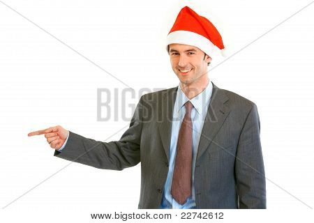 Smiling Young Businessman In Santa Hat Pointing Finger At Copy Space