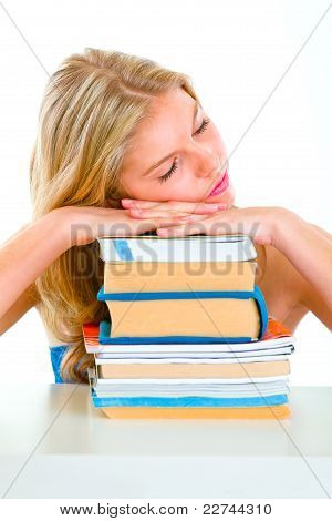 Tired Girl Sitting At Desk And Sleeping On Piles Of Books
