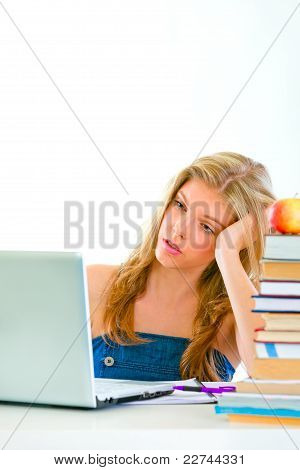 Bored Teen Girl Sitting At Table And Looking On Laptop
