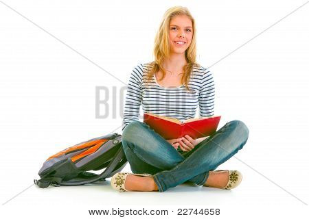 Smiling Teen Girl With Backpack Sitting On Floor And Reading Schoolbook