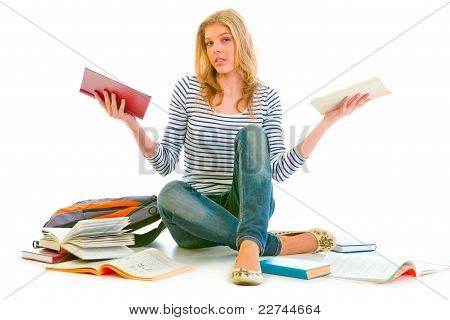 Confused Teenager Sitting On Floor Among Schoolbooks