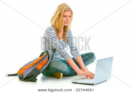 Pensive Teenager Sitting On Floor With Backpack And Using Laptop