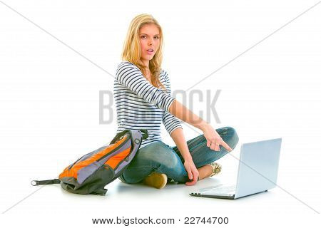 Surprised Teenager Sitting On Floor With Backpack And Pointing In Laptop