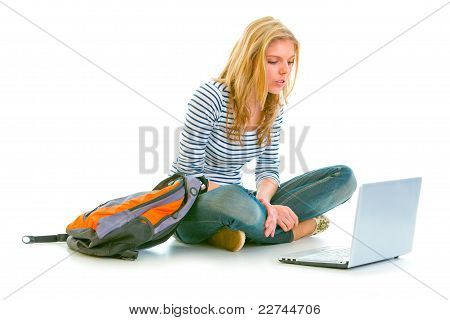 Interested Pretty Girl Sitting On Floor With Backpack And Looking On Laptop