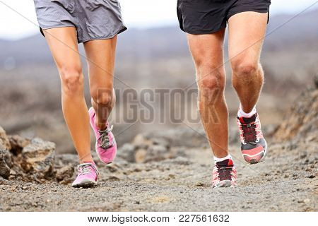 poster of Runners running shoes on trail run. Ultra running athletes legs closeup on desert trail.