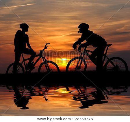 two mountain biker silhouette in sunrise