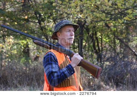Man Hunting In A Field With A Shotgun