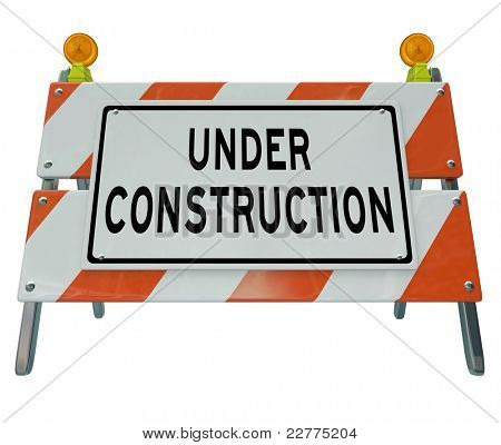 A road barricade reads Under Construction as it blocks the way and keeps you from moving forward, as a project is underway for future improvement