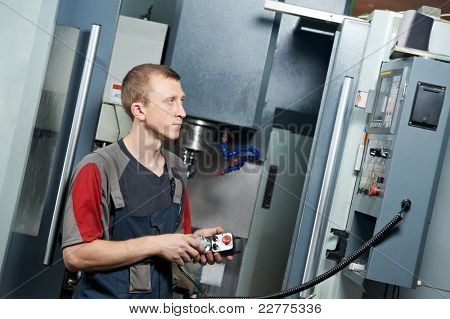 mechanical technician worker at metal machining milling center in tool workshop