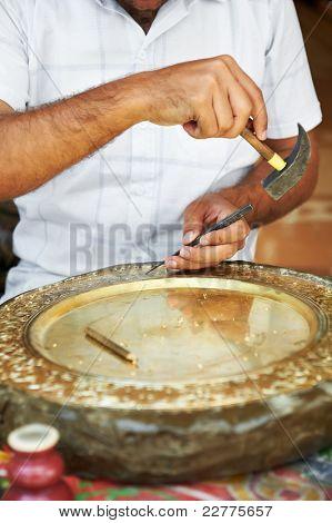 manos de chaser egipcio en el proceso de diseño oriental placa hermeticidad