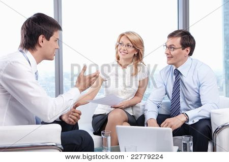 Two people listen to a young man in the office