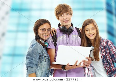 Three teenagers with laptop looking at camera